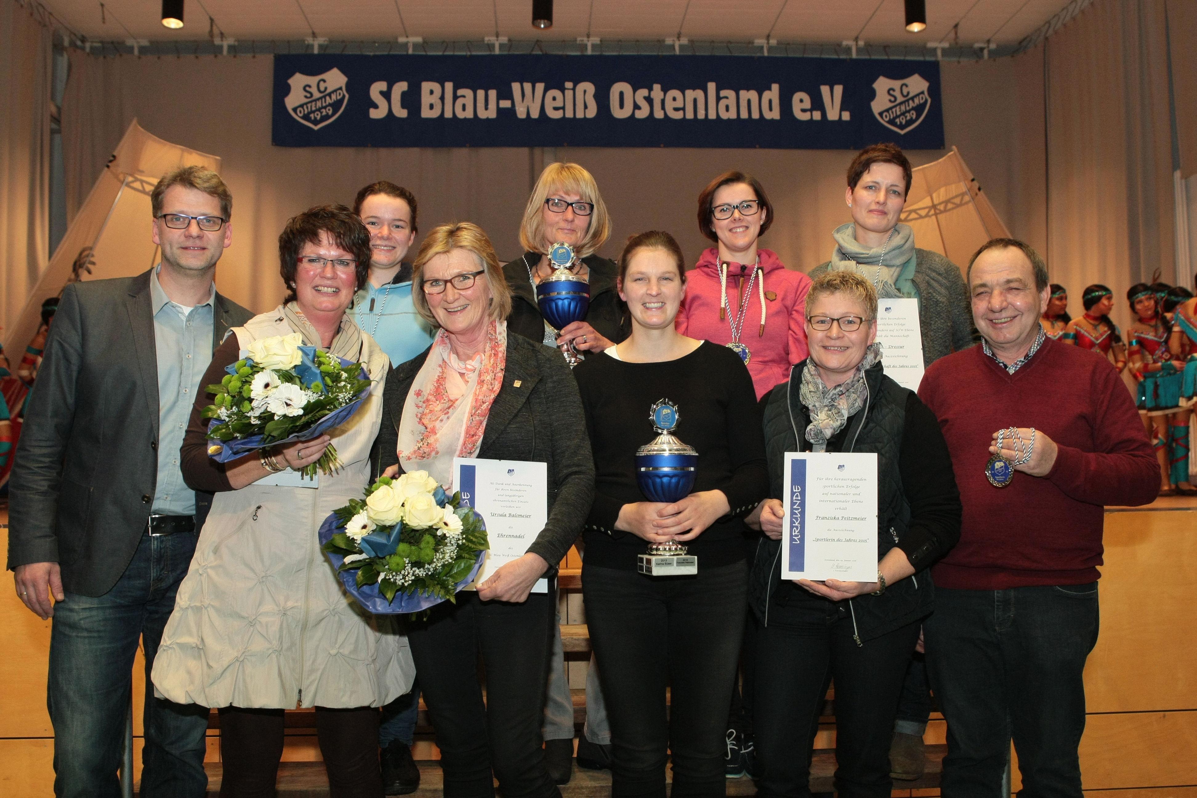 Es gratuliert der erste Vorsitzende des SC Blau-Weiß Ostenland Udo Hansjürgens (links) zur   Ehrennadel Heike Schrör und U