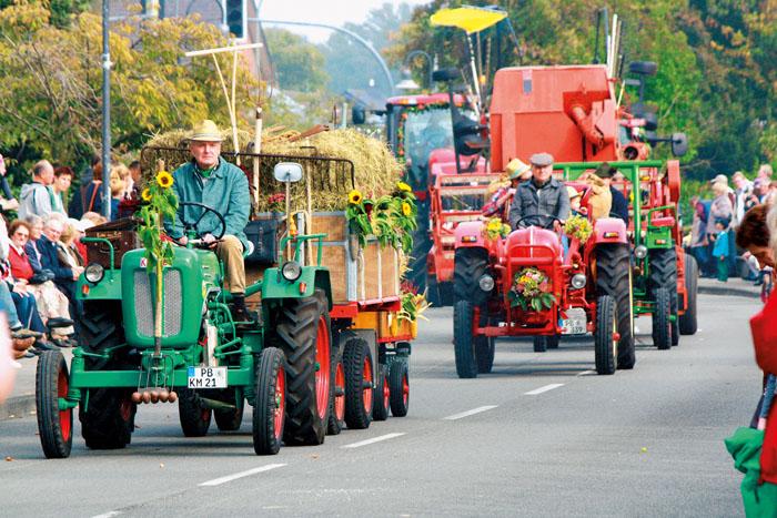 Die alten, geschmückten Landmaschinen sind immer wieder Hingucker beim großen Erntedankumzug in Westenholz. Fotos: DSA/Bruc