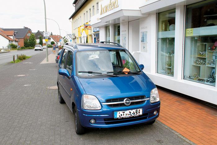 Eigentlich im Weg steht er nicht, der Opel der Geschäftsinhaberin, die Knolle gibt es dennocht. Neben der Pflasterung fängt