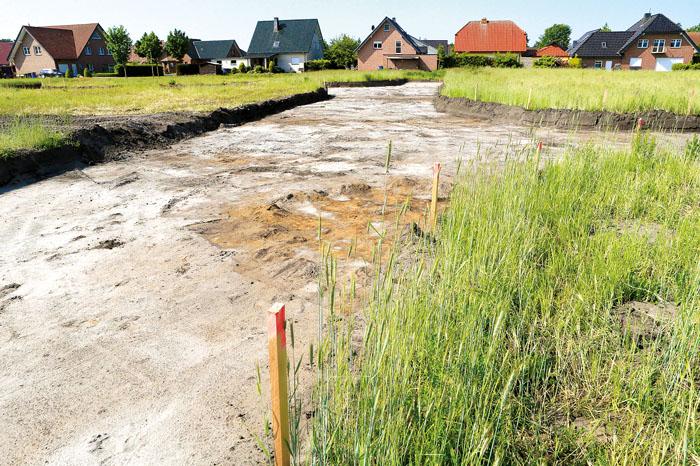 Beim Ausbaggern der Straßentrasse kamen Verfärbungen im Boden zum Vorschein. Nun muss der LWL den archäologischen Fund dok