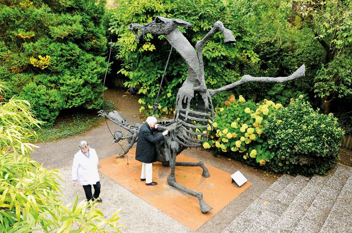 Nahezu friedvoll steht der Apokalyptische Reiter im Garten von Hilde und Wilfried Koch (von links), die ihn erfreut empfangen