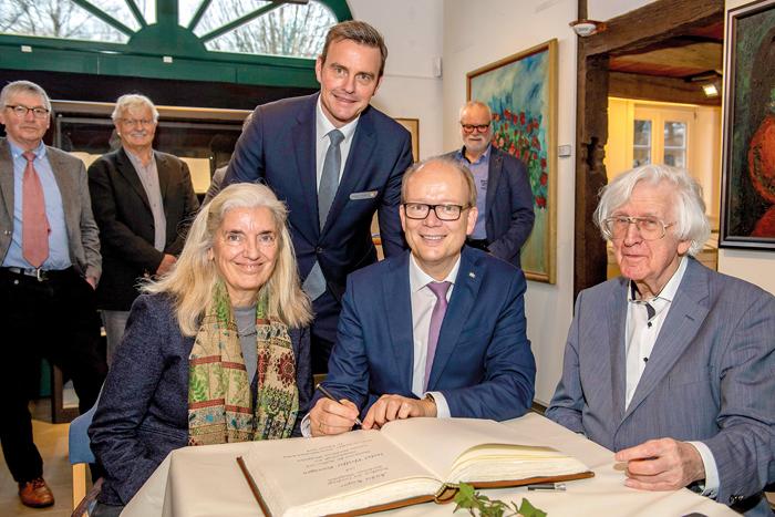 Isabell Pfeiffer-Poensgen und André Kuper (Mitte) tragen sich unter den Augen von Bürgermeister Andreas Sunder (hinten) und