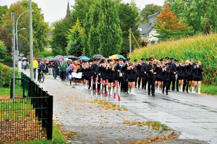 Feucht fröhlich im Regen marschieren die Klosterdörfler mit dem Spielmannszug Neuenkirchen an der Spitze über die Schulstr